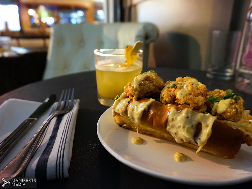 A fried oyster roll topped with house remoulade and a whiskey cocktail from The Pinewood in Decatur, Georgia.